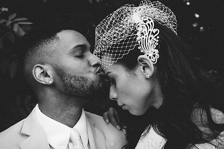 gray scale photo of man kissing a girl on forehead