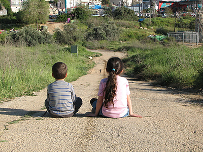two girl and boy sitting on brown road