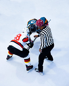 two ice hockey players and referee