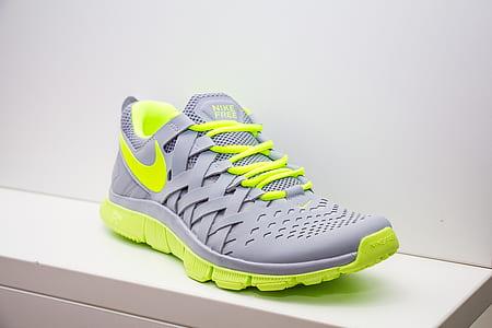 unpaired gray and green Nike running shoe