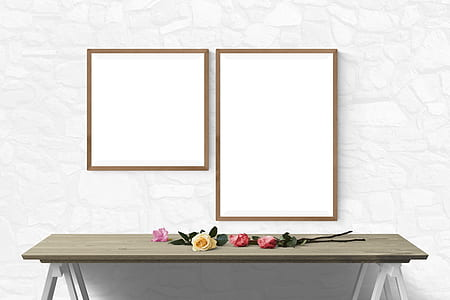 two brown wooden photo frames in front of brown wooden console table