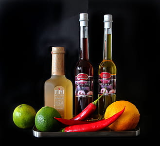 two chili peppers and limes near glass bottles