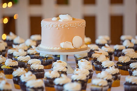 beige fondant cake surrounded with black and white cupcakes lot