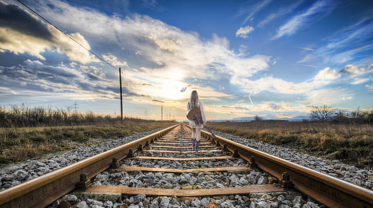 woman wearing white dress holding guitar walking on brown steel train rail road