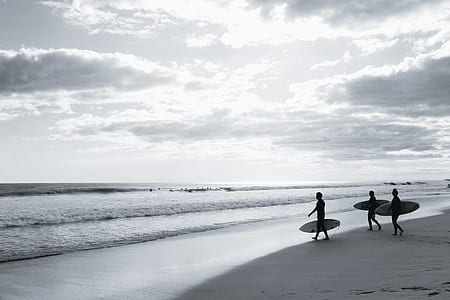 grayscale photo of three people holding surfboards walking on seashore