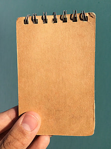 person holding brown book cover