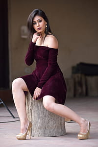woman in maroon dress sitting on wood
