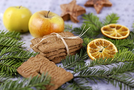 four cookies with tie beside two yellow apple fruits