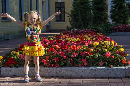 girl wearing Minnie Mouse-printed dress behind flower lot