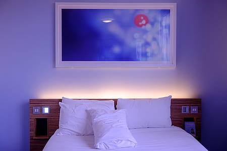 white bed linen with three white pillows