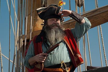 man wearing pirate suit on holding gun