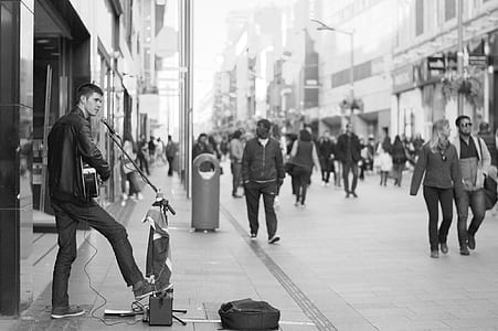 grayscale photo of man performing instrument at street