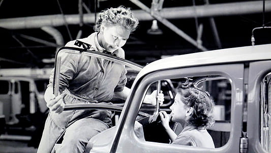 Man Carrying Car Windshield With Woman Inside a Car
