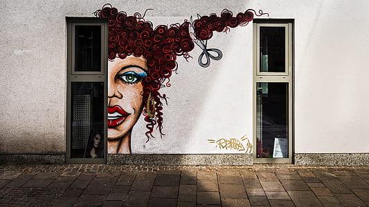 woman with brown curl hair mural between of windows