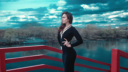 woman in black long-sleeved dress standing beside red hand rail