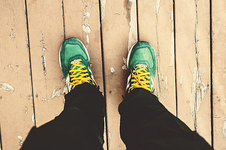 A man looking down at his green sneakers