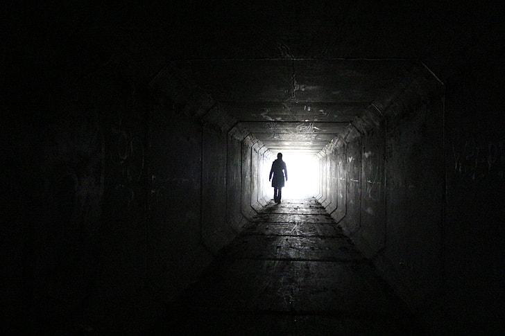 silhouette of a person toward white bright light