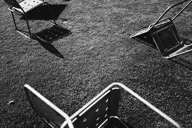 gray scale of three steel chair on ground