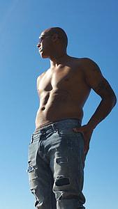 man wearing distressed blue denim jeans