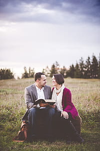 man and woman sitting on grass under blue and white sky