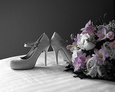 pair of women's gray stilettos beside pink and white flower bouquet