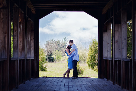 man in blue long-sleeved shirt embracing woman in blue dress