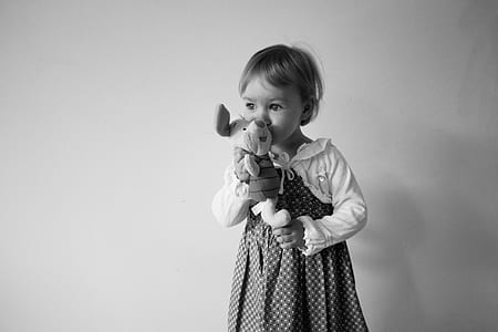 grayscale photo of girl holding Winnie The Pooh Piglet plush toy