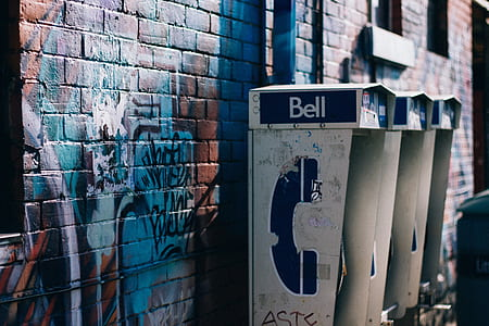three gray-and-blue telephone booth