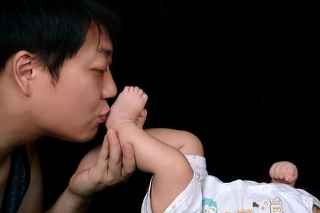 man kissing baby's foot