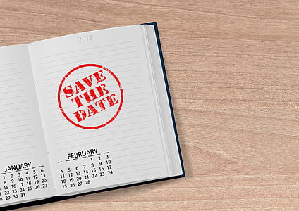 notebook with save the date stamp on top of brown wood surface