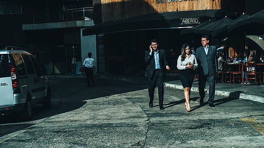 Woman in White Dress Shirt Between Men in Suit Standing on Concrete Ground