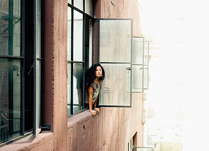 woman leaning on window during daytime