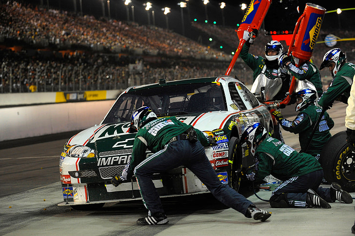 pit crew fixing white and black stock car