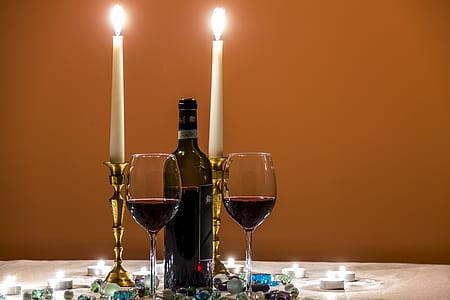 two clear wine glasses near black glass bottle