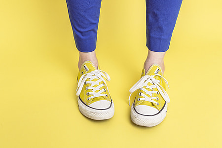 person wearing yellow Converse All Star low-top sneakers