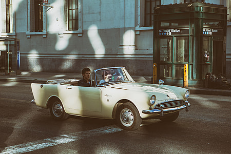 Two people sit in an open-top classic car (Sunbeam Alpine) on the streets of Manhattan, New York City