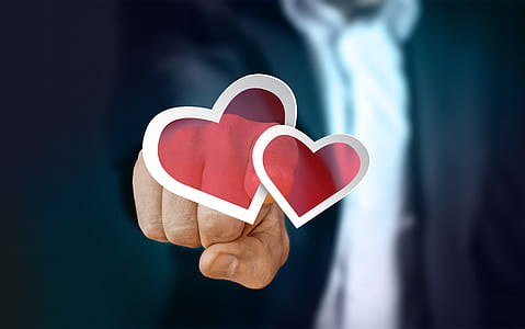 person pointing two red hearts illustration