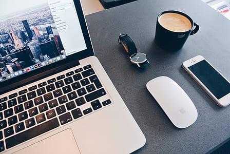MacBook pro near Apple Magic Keyboard, silver iPhone 5s, and black ceramic mug
