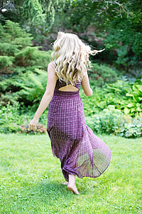 woman in purple sleeveless dress running on green grass