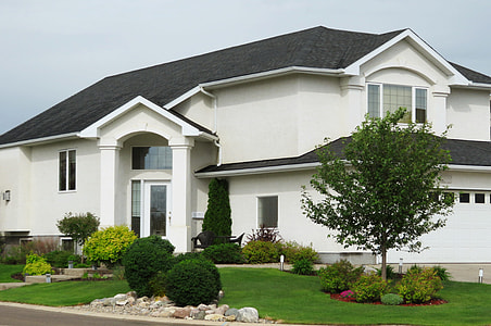 white and black concrete 2-storey house with green lawn