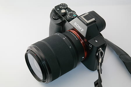 black Sony DSLR camera on white surface