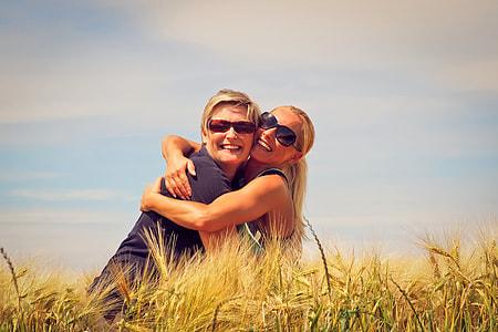 two women hugging beside brown grasses during daytime