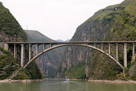 gray concrete bridge near over river near mountains
