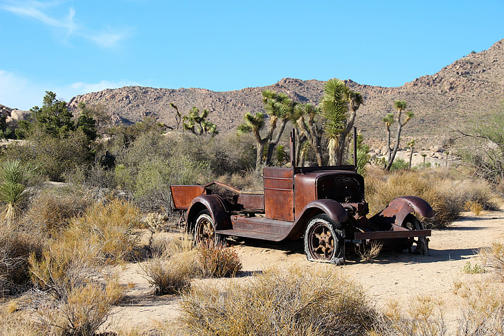 classic brown car left on desert during daytime