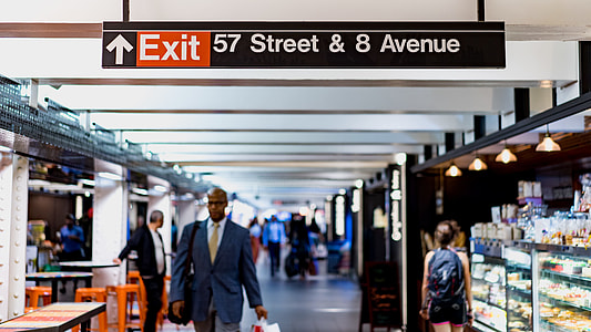 Exit 57 Street & 8 Avenue signage above people walking nearby
