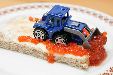 blue and grey skid loader toy on top of cake