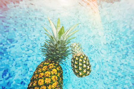two pineapples on body of water during daytime