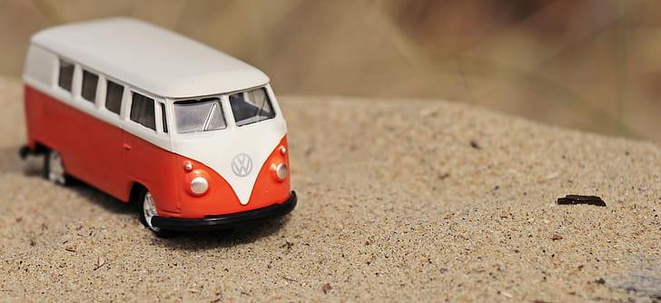 white and orange Volkswagen T2 van die-cast model on sand