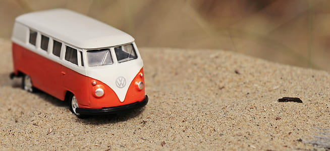 white and orange Volkswagen T2 van die-cast model on sand