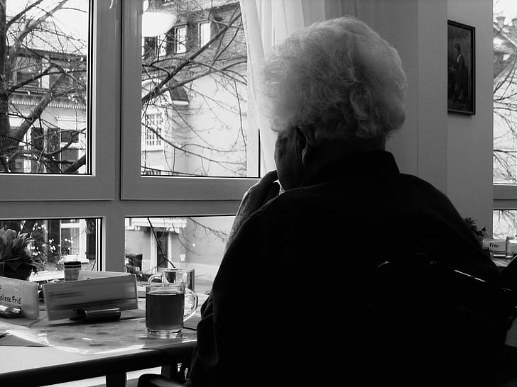 grayscale photo of person sitting near window
